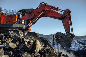 Big yellow dump truck and excavator in coal mine