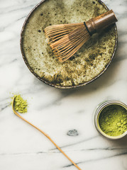 Flat-lay of Japanese tools and ceramic bowl for brewing matcha tea. Matcha powder in tin can, Chashaku spoon, Chasen bamboo whisk, Chawan bowl, cups for ceremony, grey background, top view, copy space