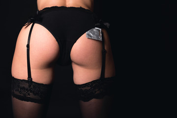 Sensuous with condom under the panties. Wearing sexy black underwear and stockings.