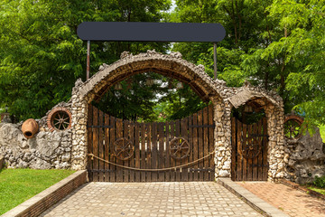 Wooden gate with a stone frame on the background of trees. Wooden gates.journey to Georgia