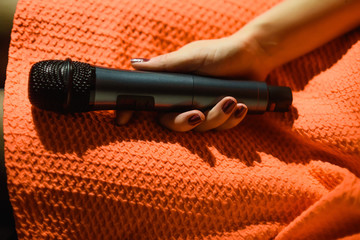 microphone in woman hand against and music notes blur colorful light background