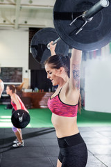 Fit Young Female Lifting Barbell In Fitness Center