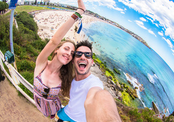 Happy traveller couple taking a selfie on vacation at beach