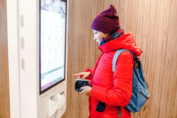 A woman orders meal in the touch screen terminal in the electronic menu in the fast food restaurant