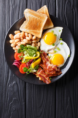 Delicious fried eggs, bacon, beans, toast and fresh vegetable salad on a plate. Vertical top view