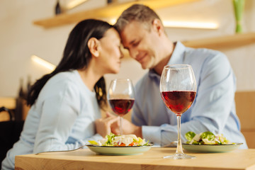 Wine. Beautiful happy disabled woman and an attractive smiling well-built man sitting in a cafe with eyes closed and holding hands and having dinner