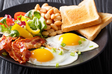 Fresh breakfast: fried eggs with bacon, beans, toast and vegetable salad on a black plate. horizontal