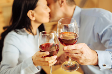 Red wine. Cheerful loving dark-haired woman and a content devoted well-built man sitting in a cafe and kissing and drinking wine