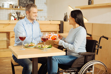 My present. Good-looking loving blond man smiling and giving a present to his attractive smiling disabled woman while having romantic dinner