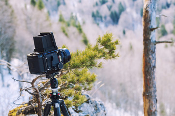Retro professional camera on a tripod, outdoor wildlife photography. Mountains, forest background.