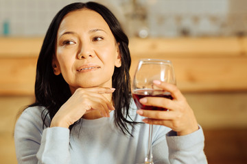 Leisure. Beautiful inspired dark-eyed woman thinking and looking in the distance while drinking red wine