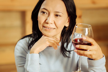 Weekend. Attractive alert dark-eyed woman thinking and looking in the distance while drinking red wine
