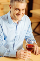 Day off. Handsome cheerful well-built man smiling and holding a glass of wine while enjoying his weekend