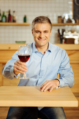 Join me. Attractive alert well-built man drinking wine and wearing a blue shirt while relaxing