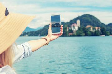 Girl photographing nice scenery on the lake.
