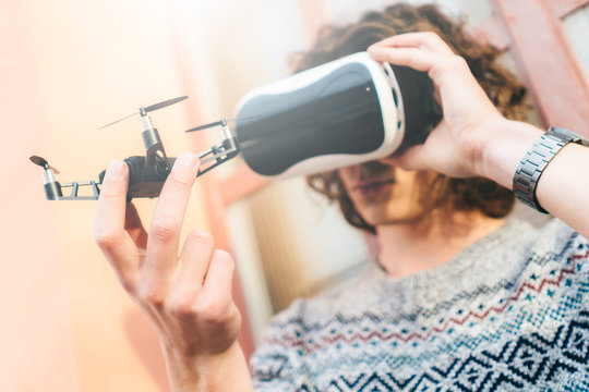 Young man wearing virtual reality glasses and holding a drone