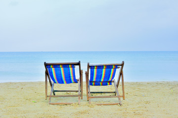 close up two casvas chair on beach with sunny day sea background in Thailand