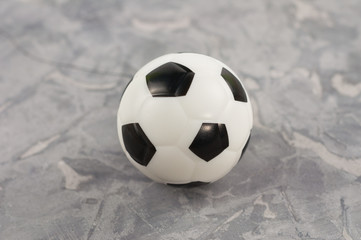 One new black and white soft rubber soccer ball on old worn cement