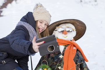 Happy young girl is taking pictures of selfie with a snowman