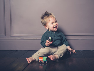 Grimacing little boy playing with wooden train