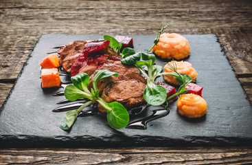 Fried sliced meat with spinach, pumpkin puree, carrots, beets and barbecue sauce on a wooden table. Side view