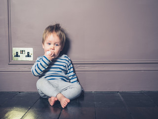 Little boy chewing on electric plug