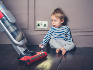 Little boy surprised by vacuum cleaner