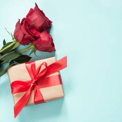 Bouquet of red roses and gift with red ribbon on pastel blue background. Valentine's card. Close up. Copy space.