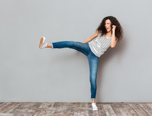 Portrait of strong young female with curly brown hair kicking invisible opponent punching with leg over grey wall