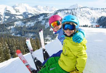 Smiling children enjoying winter vacations in mountains . Ski,Sun, Snow and Fun.