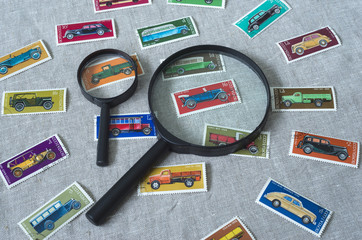 It is collection of Soviet retro stamps with motor vehicles. Two magnifying glasses and a bunch of stamps with the wheeled transport are on a horizontal surface.