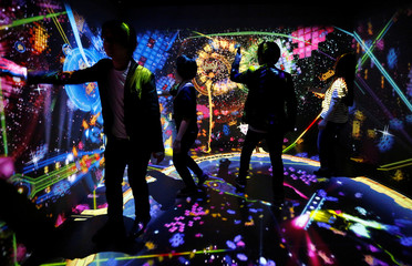 People play the VR attraction Bahamut Disco feat. Space Invaders during the preview event of the Play! Space Invaders Exhibition to celebrate the 40th anniversary of the game in Tokyo