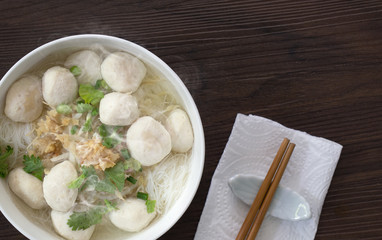 White noodle soup with pork ball in white bowl with seasoning on brown wooden floor  Chinese food