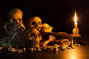 Pile of skulls on pile bone and old timber with has candle light bright splash in dark room