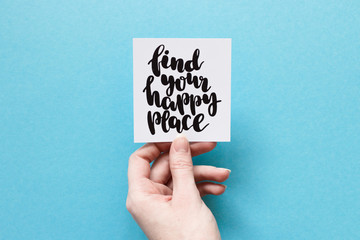 "Minimal composition on a blue background with girl's hand holding card with quote ""find your happy place"" written in calligraphy style"