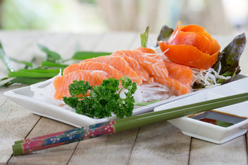 Salmon Sashimi and wasabi with black sauce Japanese food white dish on old wooden table