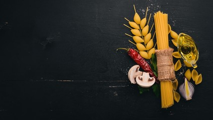 Dry pasta with fresh vegetables and spices. In the form of a spikelet of wheat on a wooden background. Top view. Copy space.
