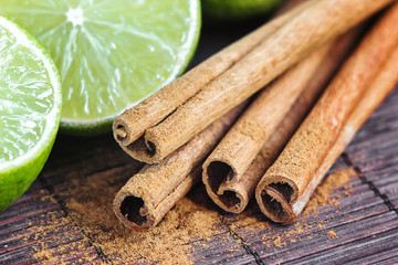 Composition citrus lime fruit and spice. Green limes whole and cut and cinnamon stick. Group of tasty fruits colorful design. Whole and half of lime pile cinnamon sticks and ground cinnamon powder
