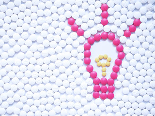 Light bulb with sparkle made by unique pink medicine pills among white ones background. Research and development in the pharmaceutical industry concept. Creative medicine idea. Copy space.