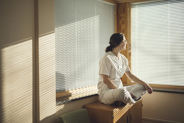 Female doctor sitting by window