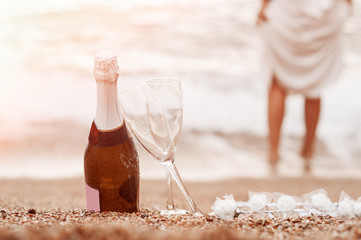 Bottle of champagne, two glasses and a diadem on the sand near the beach.
