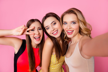 Self portrait of three funny, funky, emotional, expressive, pretty girls, gesture, show peace symbol with two fingers near eye, pink background, celebrating birthday, women's day, spring