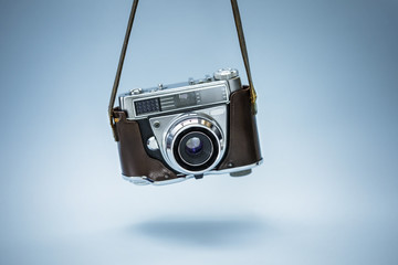 Wall Mural -  Hanging  realistic photo camera over blue background