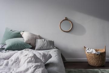 Bett mit Bettwäsche in Pastelltönen und Dekoration aus natürlichen Materialien