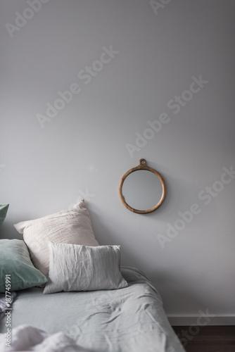 Bett mit vielen Kissen aus Samt und Leinen und einem Spiegel aus ...