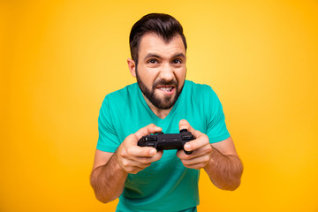 Close up photo of nervous scary fan of video games, he is holding a console, isolated on bright yellow background, copyspace