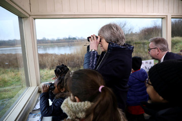 Britain's Prime Minister Theresa May watches birds from inside a bird hide as she stands with school children at the London Wetland Centre in west London
