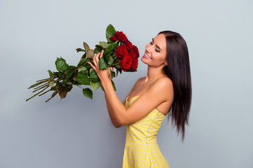 I adore flowers! Beautiful tender cute gentle lovely charming woman clothed dotted yellow dress holding luxuriant roses with long stems, isolated on grey background