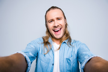 Self portrait of  attractive, cute, laughing, shouting, screaming man with bristle, stubble in jeans shirt, making video for blog in two hands on front camera over grey background