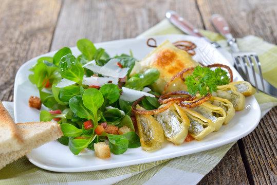 Gebratene, schwäbische Maultaschen mit Röstzwiebeln  an Feldsalat mit Croutons, Speck und Parmesan - Fried stuffed Swabian-style meat ravioli served with corn salad with croutons and bacon